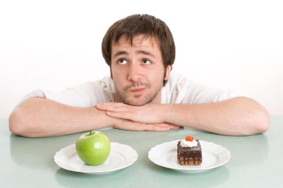 uomo che pensa se mangiare una mela o una torta